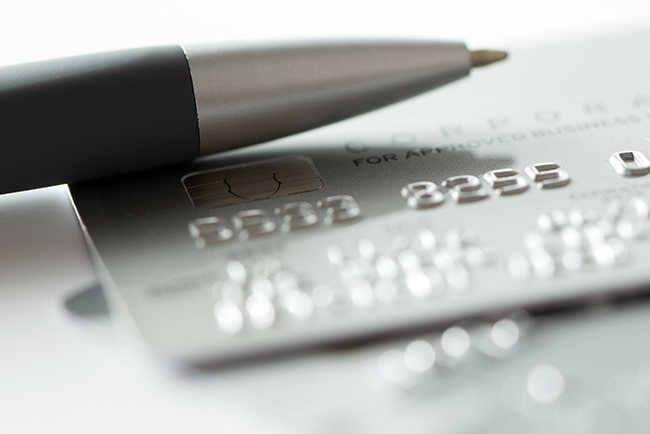 Close up of silver credit card and ballpen.